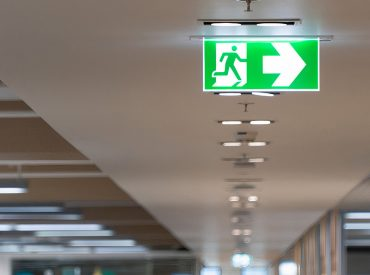 Green fire escape sign hang on the ceiling in the office.